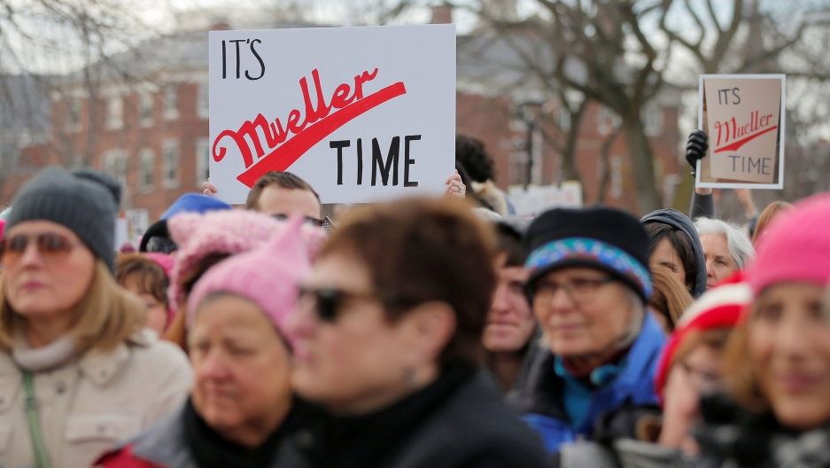 "Protesters hold signs that say ""It's Mueller time"" riffing of Miller Lite's ""Miller time"" advertisements."