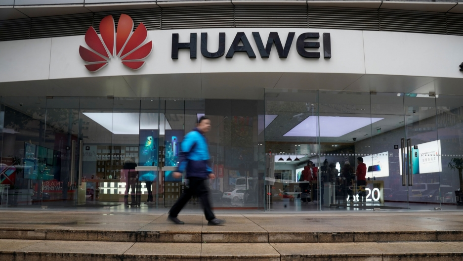 A man is shown walking by the red Huawei logo in a motion blur at a shopping mall in Shanghai, China.