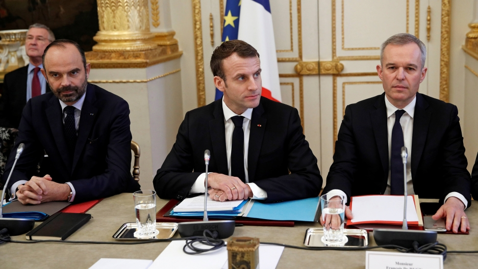 French President Emmanuel Macron, French Prime Minister Edouard Philippe, left, and French Ecology Minister Francois de Rugy dressed in suits and sitting behind a table