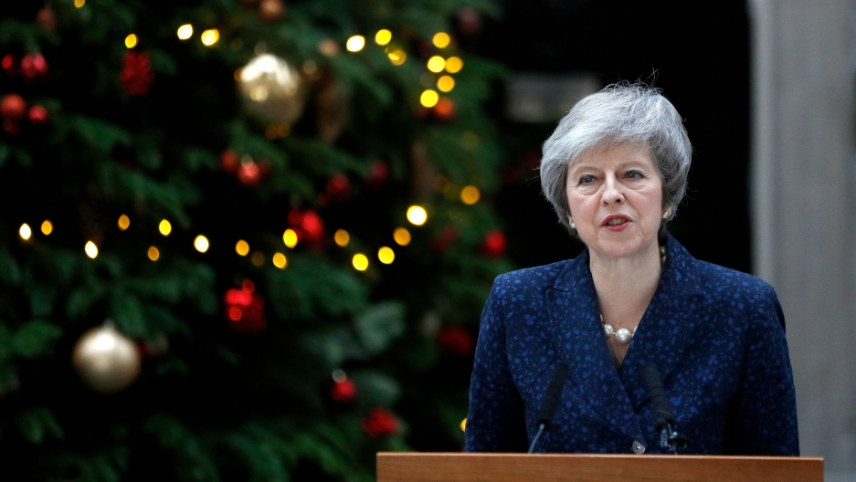 Britain's Prime Minister Theresa May is shown standing at a podium with Christmas decorations behind her.