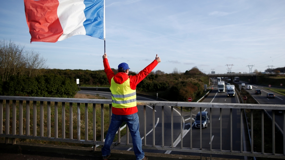 A man wearing a yellow vest and holding a French flag stands on a bridge with his arms in the air.