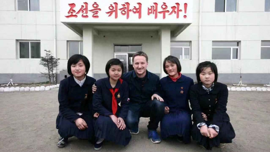 Canadian businessman Michael Spavor is shown kneeling along with several your Korean school girls in uniform in North Korea,