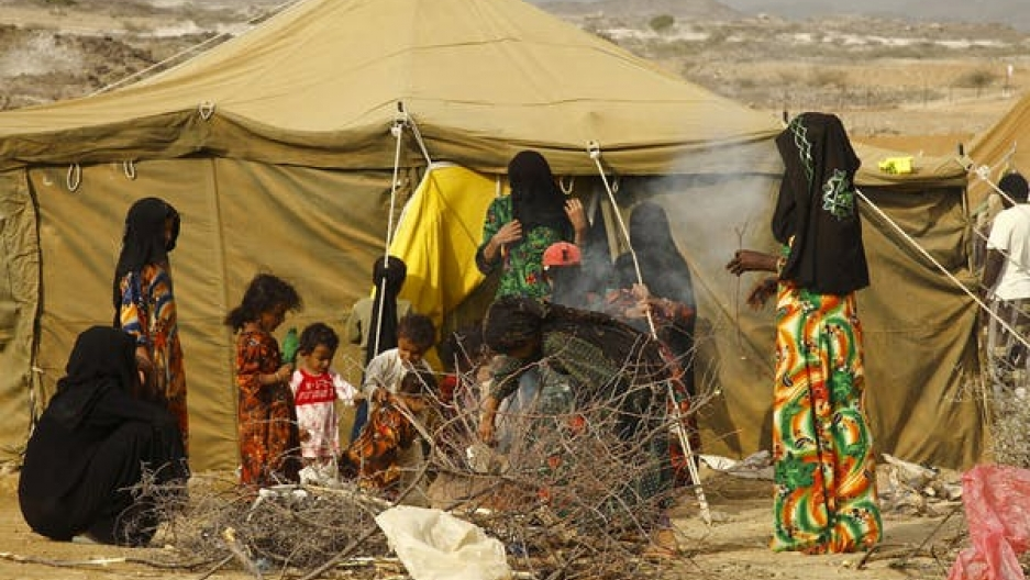Yemen women stand near a tan tent next to a pile of fire wood.