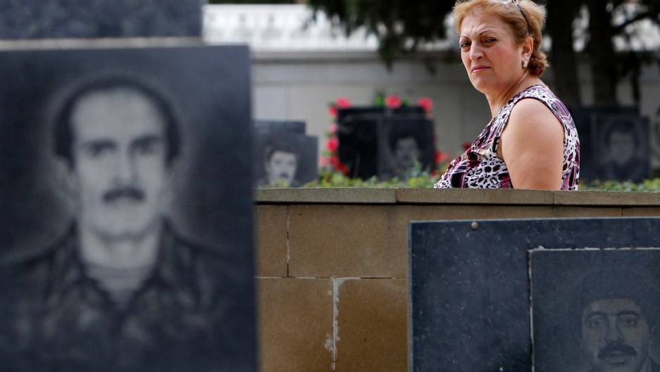 A woman walks past tombstones in the Alley of Martyrs memorial cemetery in Baku, Azerbaijan, Sept. 8, 2012.