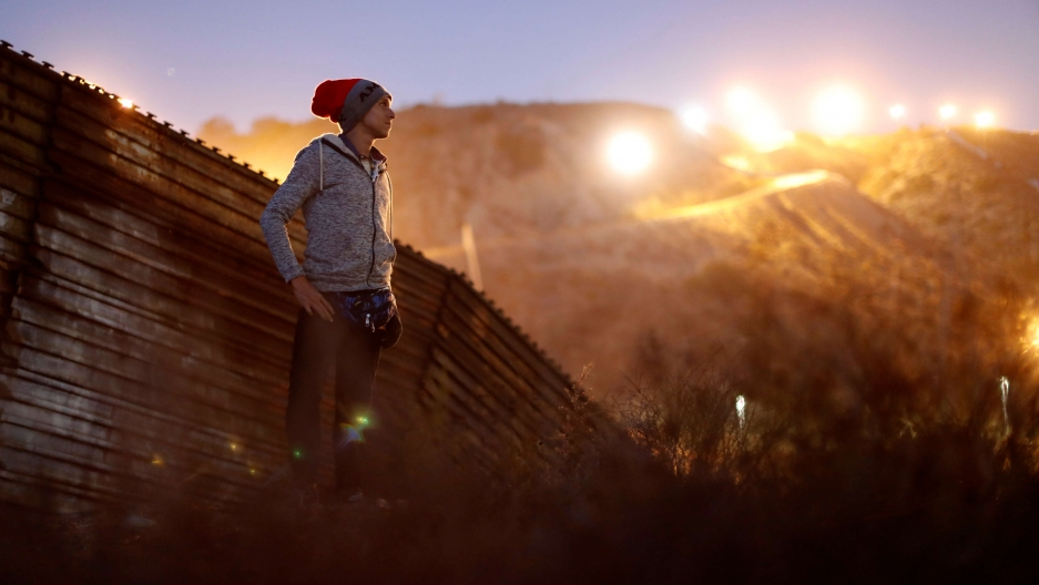 a migrant from honduras stands in front of the border wall with the sun shining behind