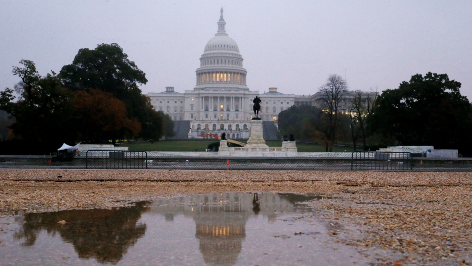 US Capitol building is seen reflected in a puddle at sunrise on the day of the US midterm election