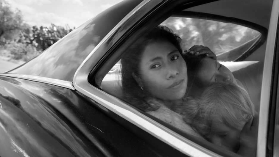 a black and white photo of a woman looking out a car window