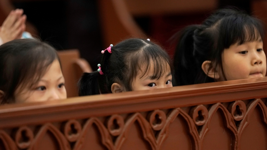 Three girls peer over the pew in church in China.