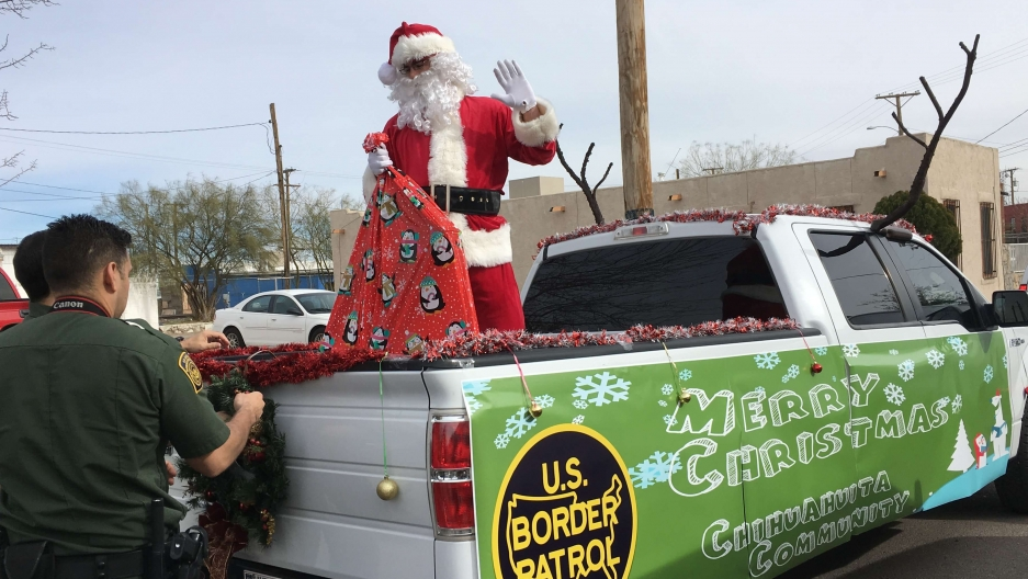 a man wearing a santa claus costume arrives in a pickup truck in el paso