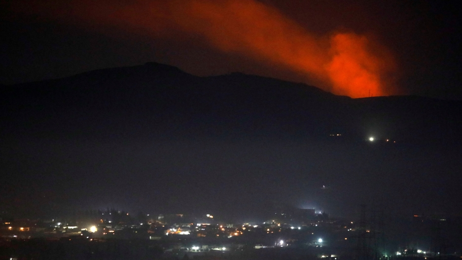 Smoke is shown with red backlighting rising past a mountain range as seen from the Damascus, Syria, countryside.