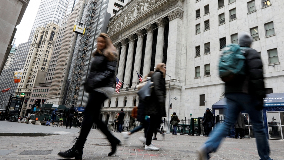 People are shown in blurred motion walking in front of the New York Stock Exchange.