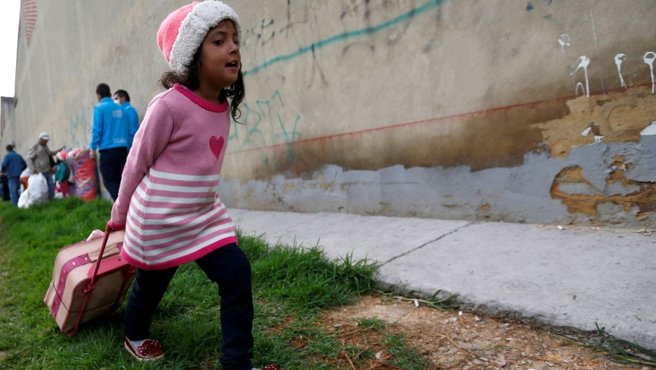 A Venezuelan migrant girl wearing a pink sweater with a heart on it, is shown heading to the exit of a makeshift camp with her belongings in Bogota, Colombia.