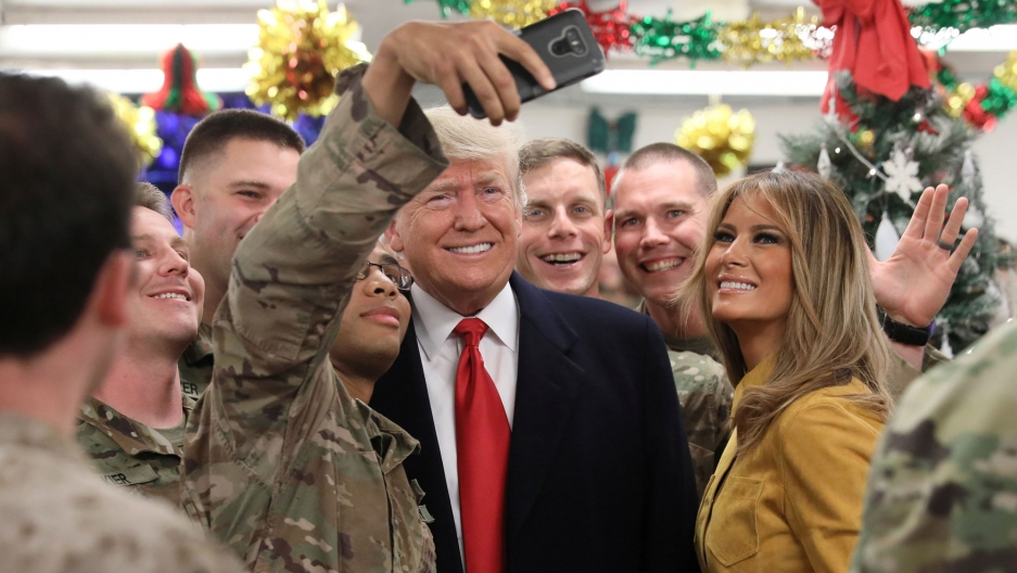 President Donald Trump and First Lady Melania Trump are shown surrounded by troops in camoflage while one soldier takes a selfie.