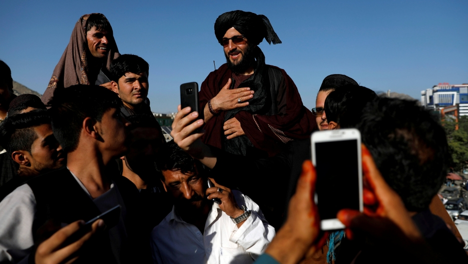 a taliban being carried on people's shoulders while others take photos