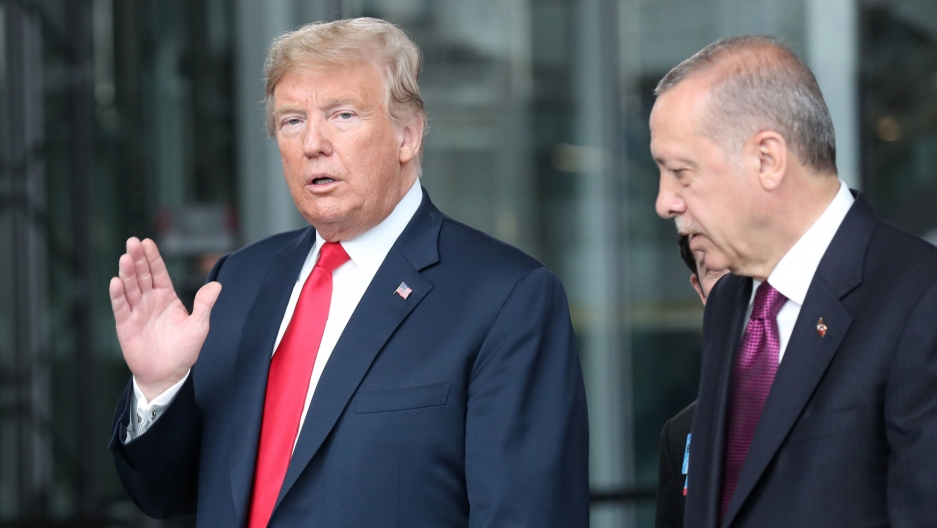 President Donald Trump is shown walking with Turkey's President Recep Tayyip Erdoğan with his right hand raised waving at the camera.