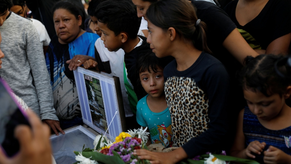 People crowd next to the coffin with a young person in a blue shirt with a tear in their eye, during her funeral, in Tegucigalpa, Honduras in July.