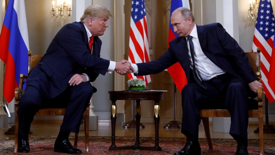 Trump and Putin shake hands.
