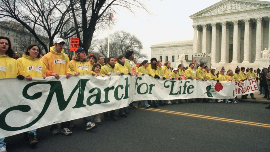 Anti-abortion activists march in front of the US Supreme Court with banner.