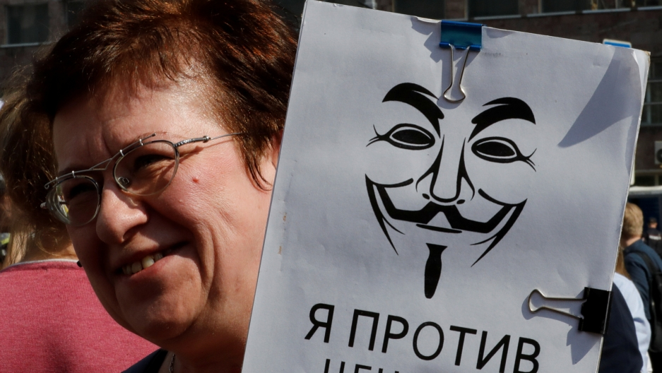 "A woman holds a sign in Russian that says ""I'm against censorship."""