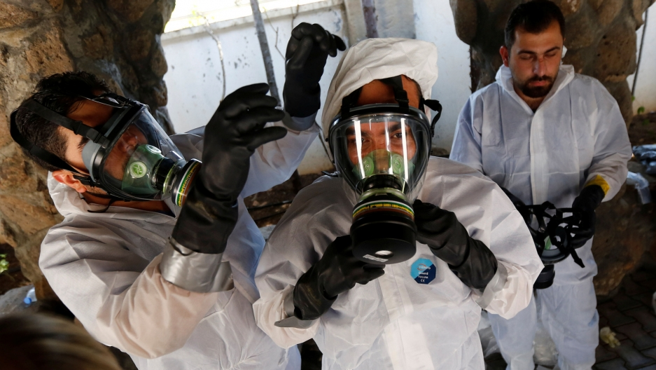 Three Syrian medical staff wear gas masks in a chemical weapons attack training.