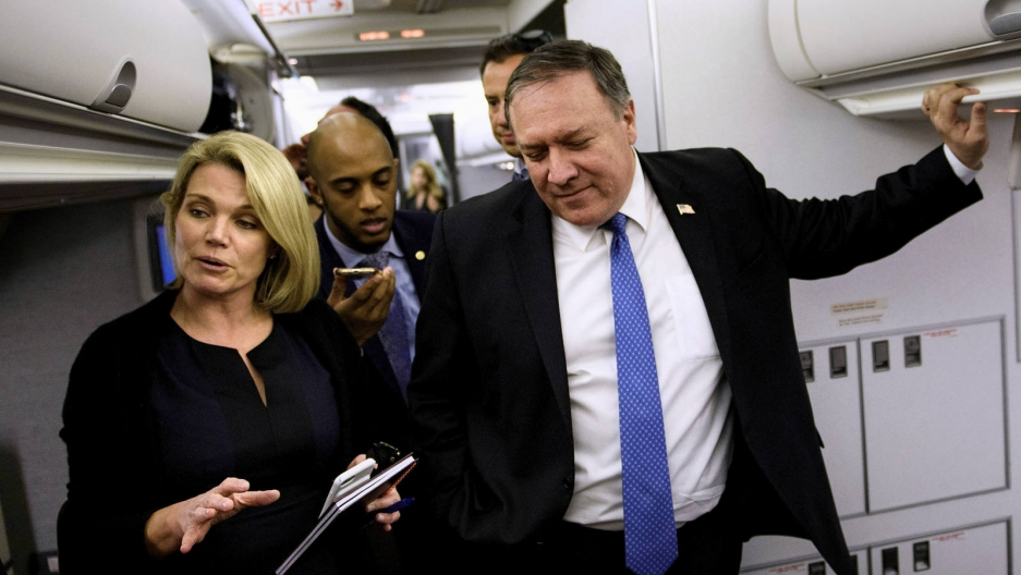 Heather Nauert and Mike Pompeo wear navy blue suits and speak with reporters inside a plane.