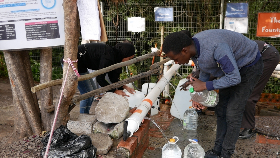 Cape Town residents gather to collect water at a spring with makshift spigots ear Table Mountain. It's one of dozens of open springs across the city where residents come to collect extra water to add to their meager daily quota of 13 gallons.