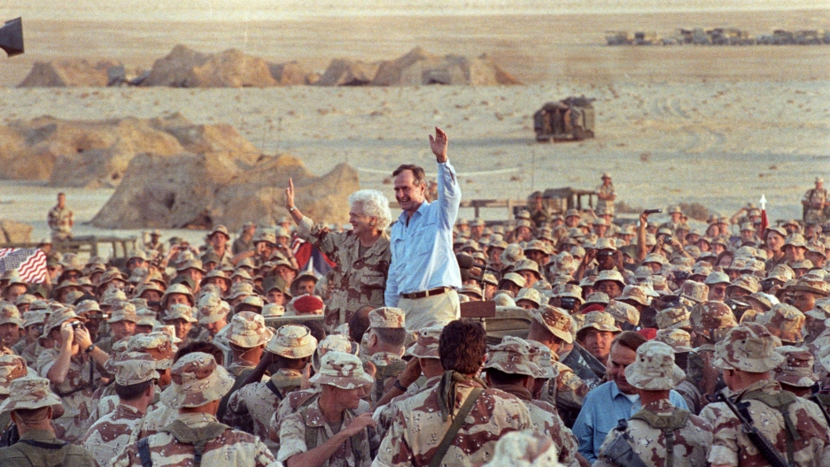 President HW Bush and his wife wave while surrounded by a large crowd of soldiers wearing tan and khaki fatigues
