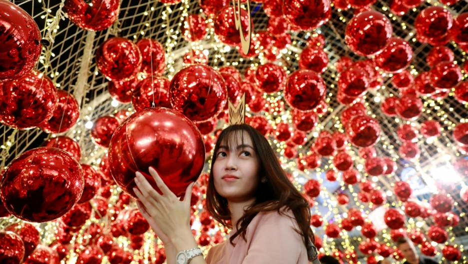 A woman poses for a photo surrounded by red Christmas ornaments in Bangkok, Thailand.