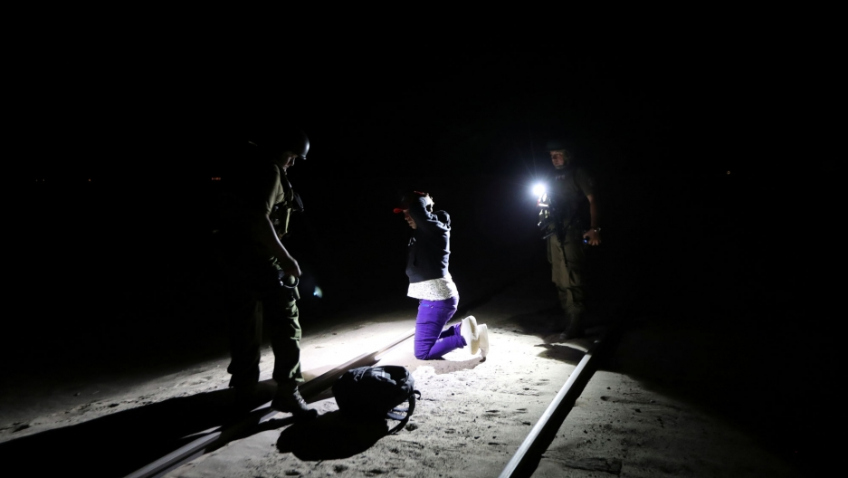 Migrant Yoniel Torres is shown wearing purple pants and handcuffed at theChilean and Peruvian border in Arica, Chile.