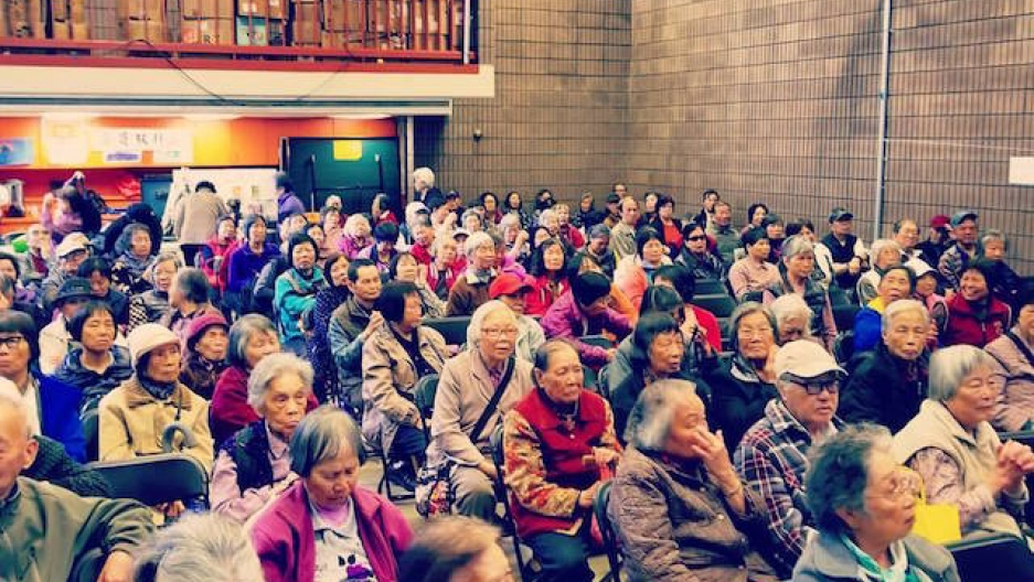 A room full of mostly elderly Asian residents of San Francisco's sit in a large room as they attend a talk on protecting themselves from immigration enforcement.