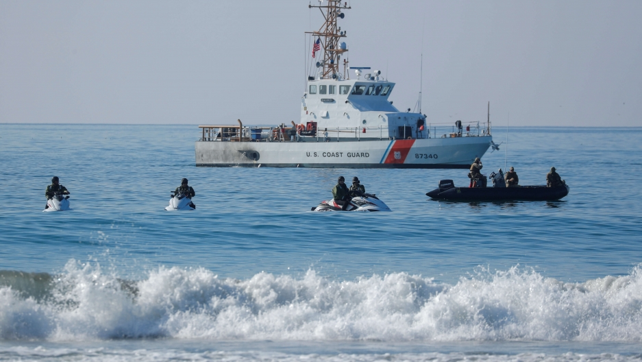 a cost guard ship with people on jet skis in front