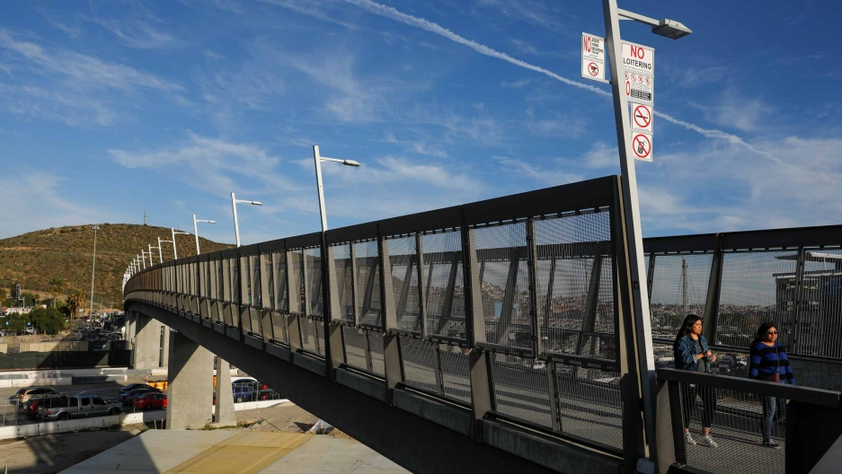 Pedestrians cross a tall bridge