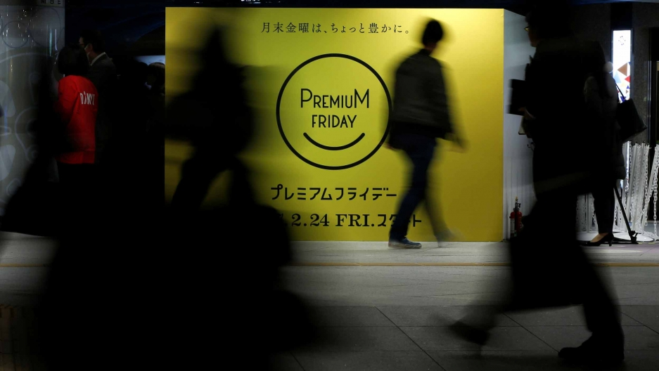 """People walk by a bright yellow sign that says """"premium day"""" in a smiley face."""