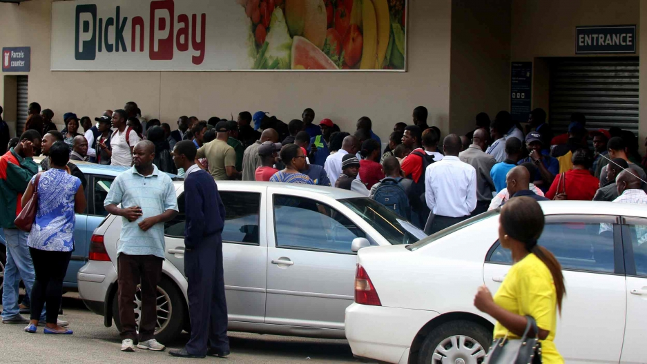 A crowd of people stand outside a closed supermarket