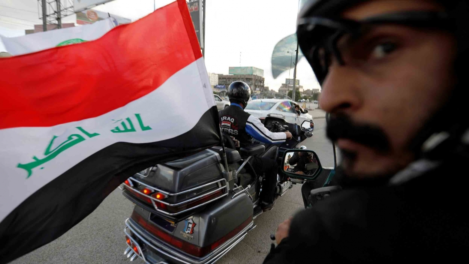 An Iraqi flag blows in the wind from the back of motorcycle.