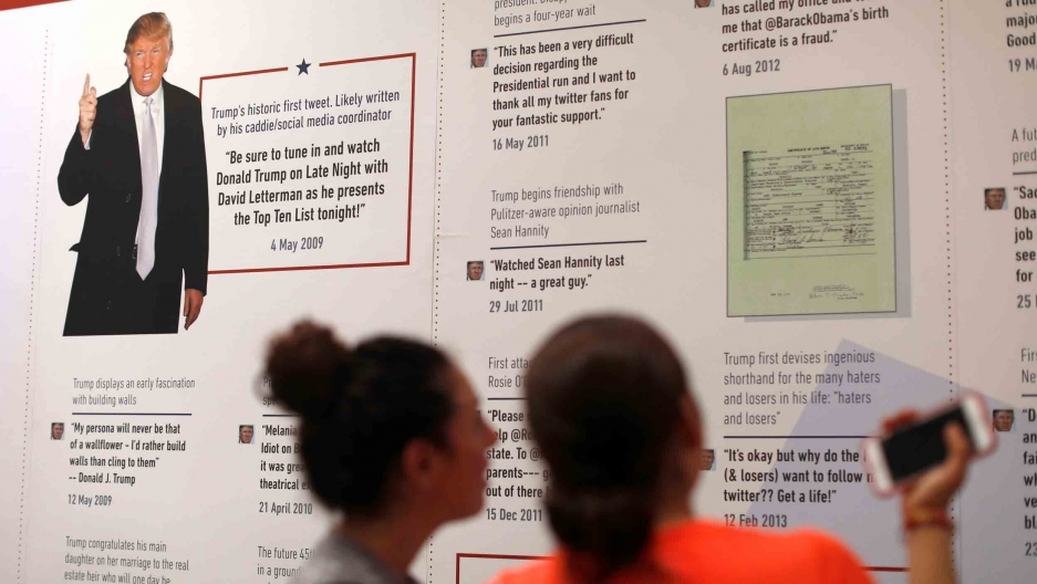 Two people look at a museum displaying showing a history of Donald Trump's tweets