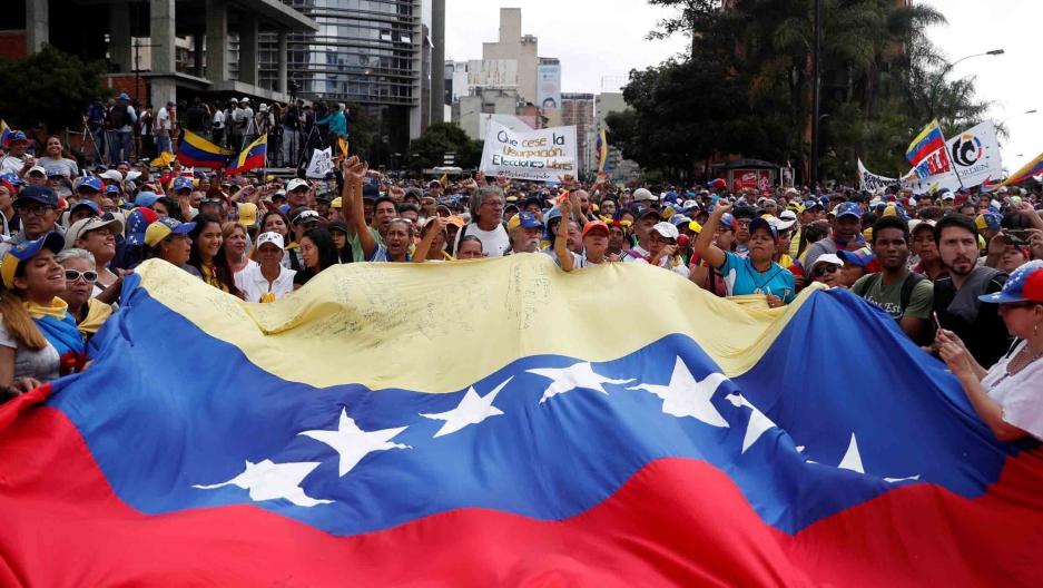 Hundreds of protests stand behind a massive Venezuelan flag