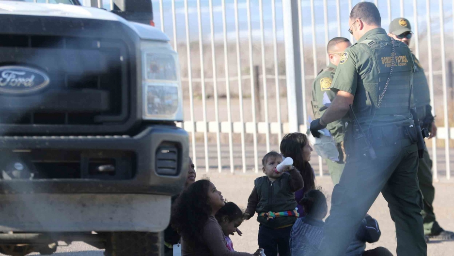 A migrant woman and her children sit beside a truck while three border patrol officers take them into custody