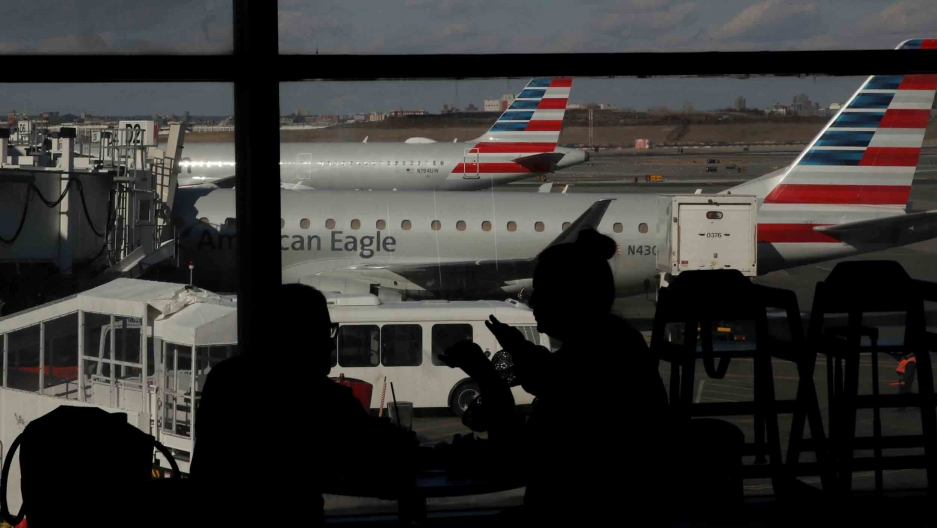 People waiting in an airport are silhouetted against big windows. Outside, planes are waiting next to gates.