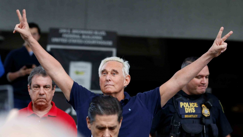 Roger Stone puts his hands up and makes peace signs as he walks to microphones