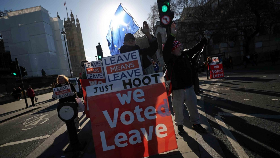 "Protesters hold signs reading, ""We voted leave"" and ""Leave means leave."""