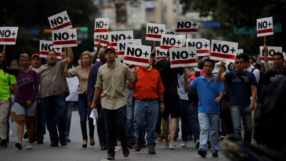 "A group of people hold signs that say ""No dictadura"" as they march down a street."