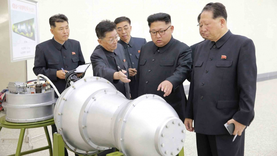 Kim Jong-un inspects a large metal piece of equipment with others around him.