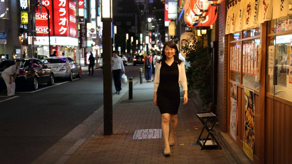 A woman in a black dress stands on a city street in Japan. Signs with Japanese characters are behind her, on restaurants and billboards.
