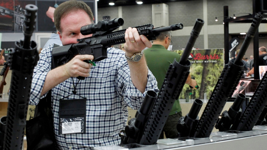 A man holds the sight of a rifle up to his right eye. More rifles are in racks on his left and right.