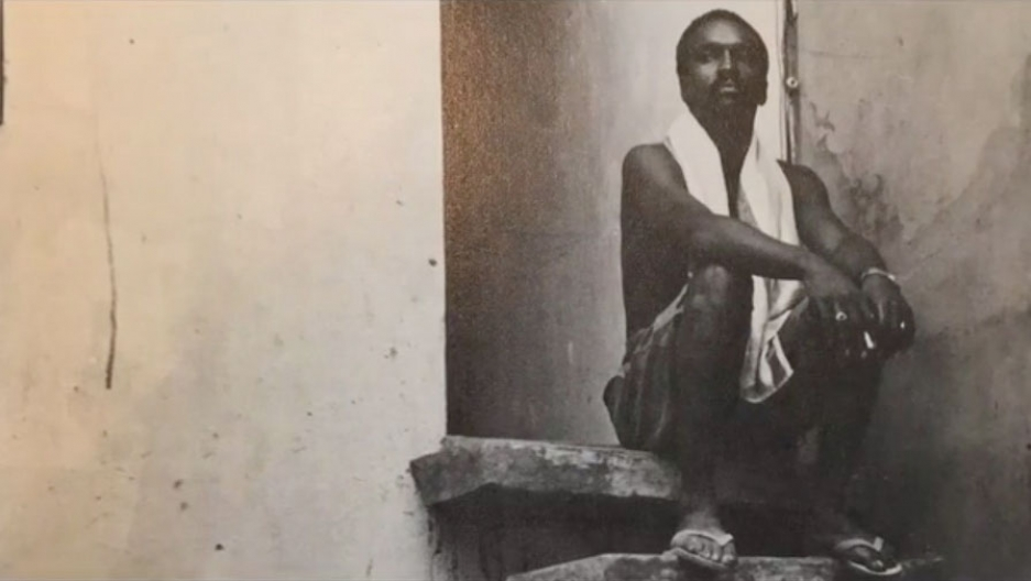 An African American man sits on a stair step with a towel around his neck