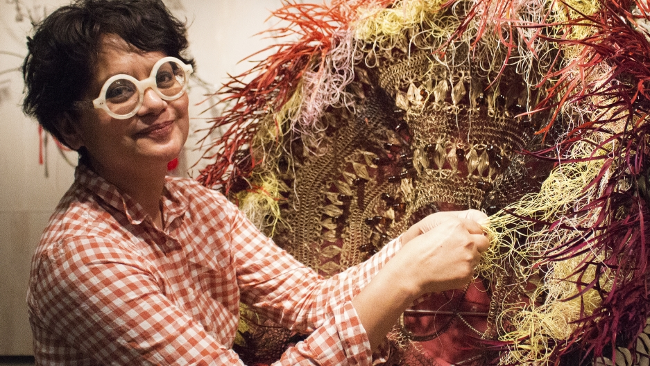 "Rina Banerjee works on her sculpture ""Excessive Flower."""