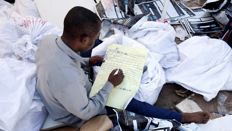 a man without shoes, sits on a big pile of papers while he examines voting materials