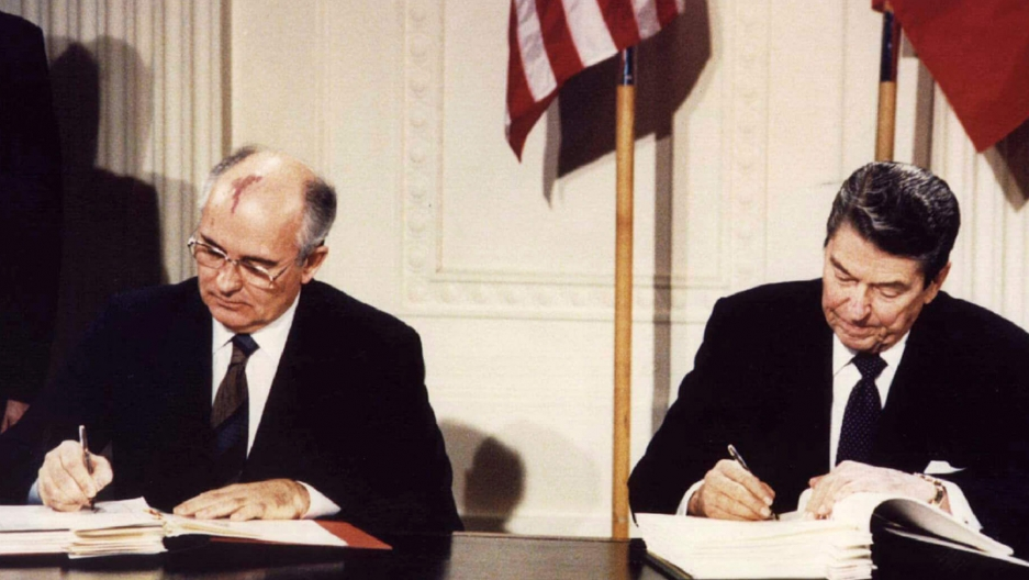 Two leaders sit at a desk signing a document.