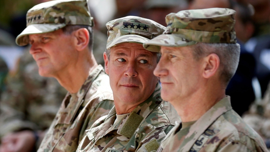 US Army General Scott Miller is shown center looking over his left shoulder and wearing fatigues.